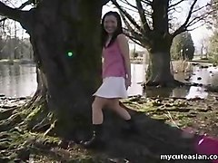 cute asian teen dances around the duck filled pond
